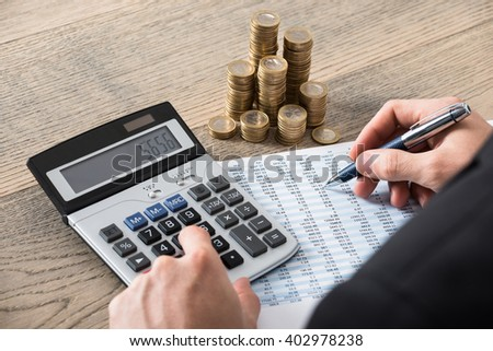 Close-up Of A Businessman Calculating Financial Report With Stack Of Coins On Desk In Office - stock photo
