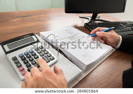 Close-up Of A Businessman Calculating Invoice Using Calculator At Desk In Office - stock photo