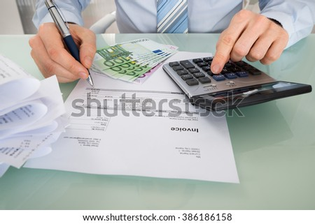 Close-up Of A Businessman Calculating Invoice With Euro Banknotes At Desk - stock photo
