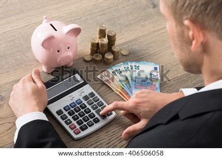 Close-up Of A Businessman Calculating Savings Using Calculator At Desk In Office - stock photo