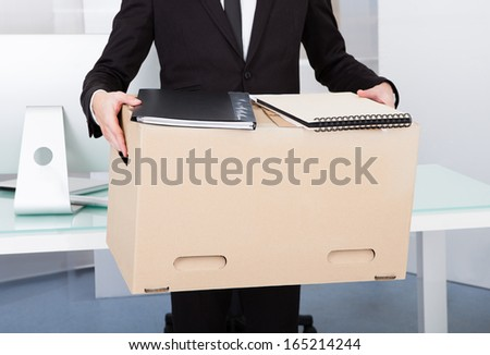 Close-up Of A Businessman Carrying Box At His Workplace - stock photo