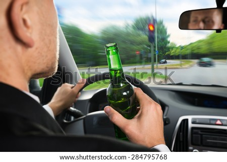 Close-up Of A Businessman Drinking Beer While Driving Car - stock photo