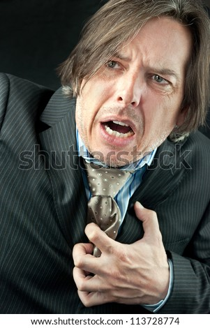 Close-up of a businessman experiencing a heart attack. - stock photo