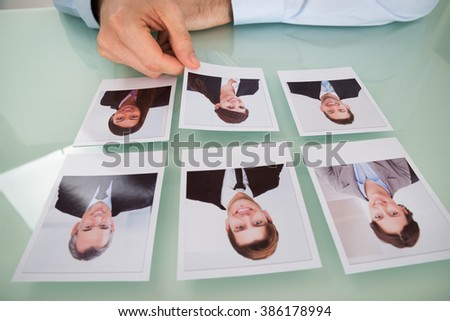 Close-up Of A Businessman Hand Choosing Photograph Of A Candidate - stock photo