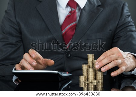 Close-up Of A Businessman Hand Counting Coins Using Calculator