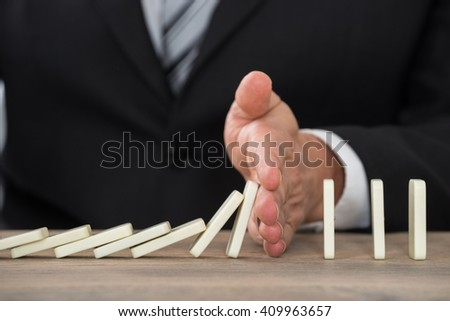 Close-up Of A Businessman Hand Stopping Dominoes From Falling On A Desk In Office
