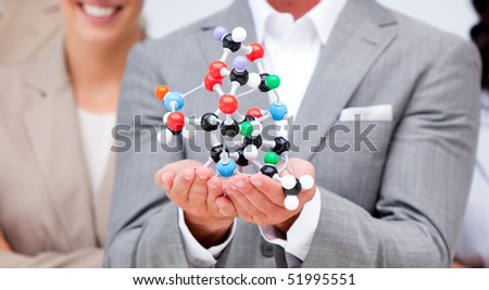 Close-up of a businessman holding a molecule with his team in the background - stock photo