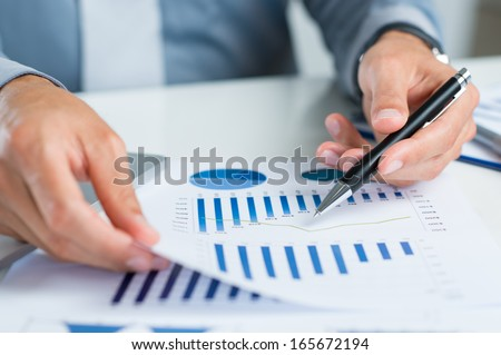 Close Up Of A Businessman Holding Graph Paper And Pen - stock photo