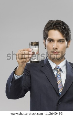 Close-up of a businessman looking at an hourglass