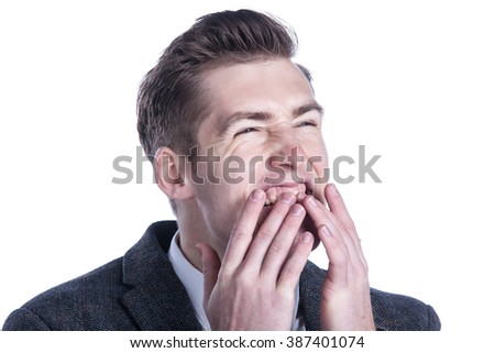 Close-up of a businessman making funny face over white background.