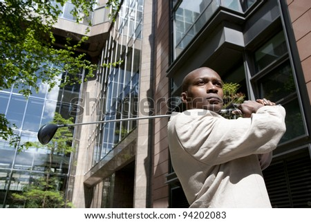 Close up of a businessman playing golf in the financial district. - stock photo