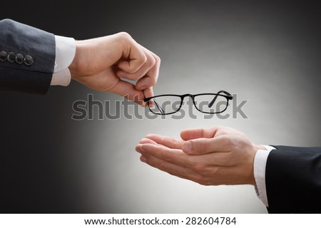 Close-up Of A Businessman's Hand Giving Eye Glasses To His Colleague - stock photo