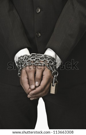 Close-up of a businessman's hands locked with chains - stock photo