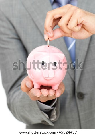 Close-up of a businessman saving money in a piggy-bank against a white background - stock photo