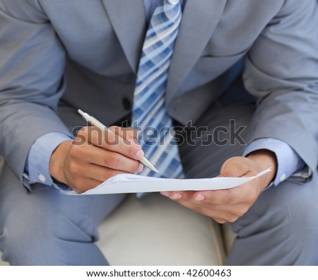 Close-up of a businessman sitting and writing on a paper