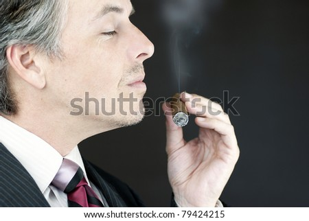Close-up of a businessman smelling a cigar, side view. - stock photo