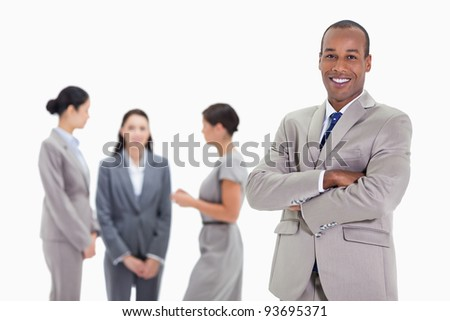 Close-up of a businessman smiling and crossing his arms with three female co-workers talking in the background - stock photo