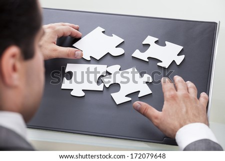 Close-up Of A Businessman Solving Jigsaw Puzzle - stock photo