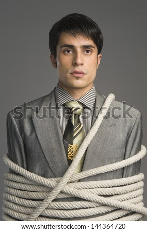 Close-up of a businessman tied up with ropes - stock photo