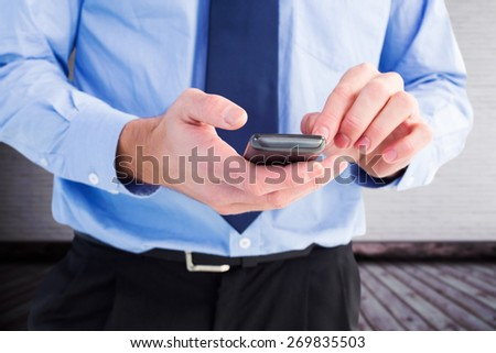 Close up of a businessman using a smartphone against grey room