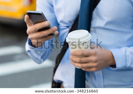 Close up of a businessman using mobile phone and holding paper cup. Close-up detail of a businessmanâ??s hand holding paper cup and using a smartphone while walking on the road. Man going at work.