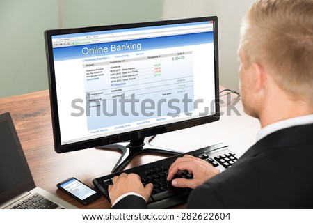 Close-up Of A Businessman Using Online Banking Service On Computer At Office - stock photo