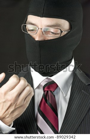 Close-up of a businessman wearing a balaclava inspecting his nails - stock photo
