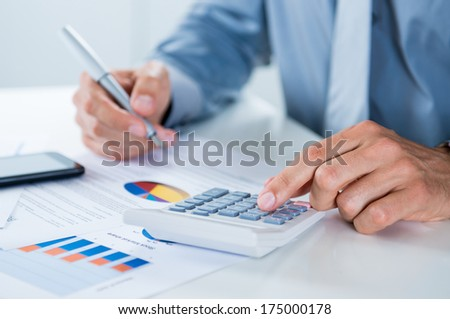 Close Up Of A Businessman With Documents At Desk Doing Calculations - stock photo