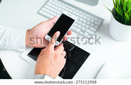 close-up of a businessman working with a tablet pc and mobile phone - stock photo