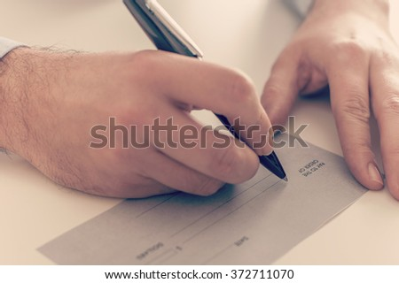 Close up of a businessman writing a payment check - stock photo