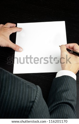 Close-up of a businessman writing, shot from over the shoulder. - stock photo