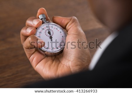 Close-up Of A Businessperson Hand Holding Stop Watch