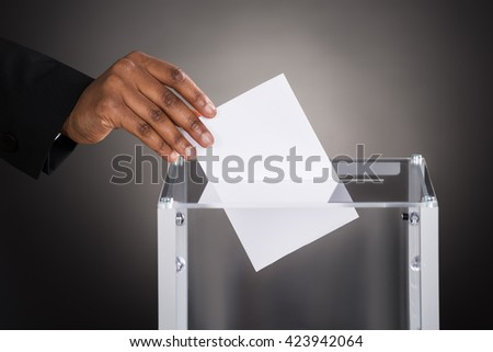Close-up Of A Businessperson Hand Inserting Ballot In Glass Box Against Gray Background - stock photo