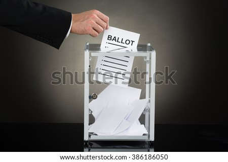 Close-up Of A Businessperson Hand Putting Ballot In Glass Box - stock photo