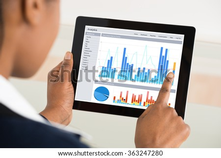 Close-up Of A Businesswoman Analyzing Graph On Digital Tablet - stock photo