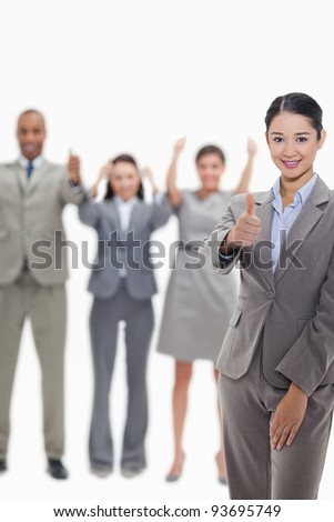Close-up of a businesswoman approving with hand gesture with enthusiastic co-workers raising their arms in the background