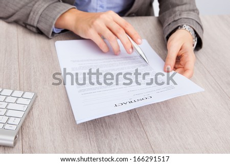Close-up Of A Businesswoman At Desk Holding Contract Paper