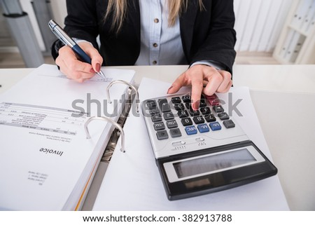 Close-up Of A Businesswoman Calculating Invoice With Calculator - stock photo
