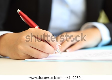 Close up of a businesswoman hands writing in a document on a desktop at office