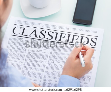 Close-up Of A Businesswoman Holding Pen Reading Classifieds On Newspaper - stock photo