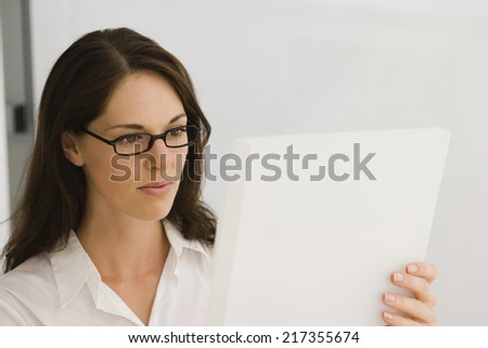 Close-up of a businesswoman looking at a blueprint - stock photo