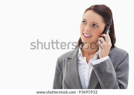 Close up of a businesswoman looking up while smiling on the phone against white background
