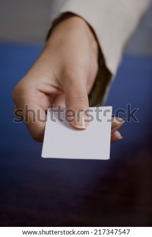 Close-up of a businesswoman's hand holding a blank card