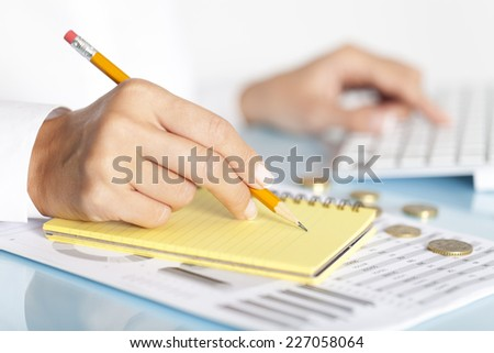 Close-up of a businesswoman's hand with a pencil writing something.