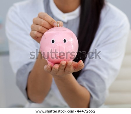 Close-up of a businesswoman saving money in a piggybank in the office - stock photo