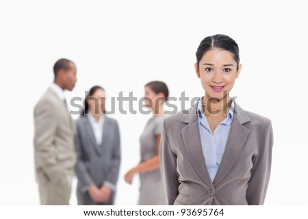 Close-up of a businesswoman smiling with co-workers talking in the background