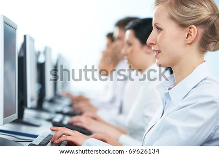 Close-up of a businesswoman working on computer among her colleagues - stock photo
