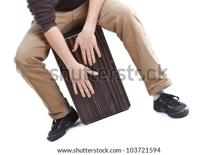 Close-up of a cajon, man's legs and hands are shown as he's playing the instrument - isolated on white - stock photo