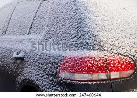 Close-up of a car covered by snow in a winter day. - stock photo