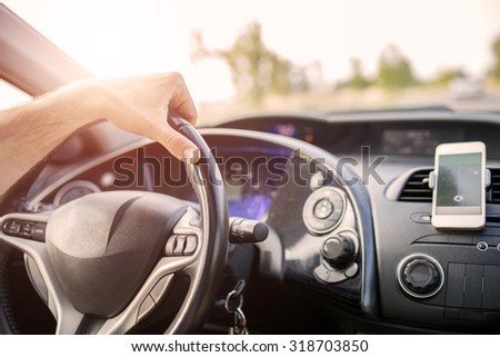 Close up of a car dashboard with navigation in smart phone - stock photo
